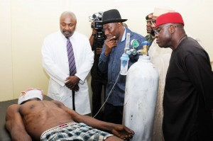 Nigerian President Goodluck Jonathan (C) and Nigerian Senate President David Mark (R) look at an injured victim of a bomb attack receiving medical treatment at a hospital in Abuja on April 14, 2014. A bombing at a bus station packed with morning commuters on the outskirts of Nigeria's capital killed 71 people and wounded 124 on April 14, with the president blaming the attack on Boko Haram Islamists. The explosion rocked the Nyanya station south of Abuja at 6:45 am (0545 GMT), leaving body parts scattered across the terminal and destroying dozens of vehicles. AFP PHOTO/STRINGERSTRINGER/AFP/Getty Images